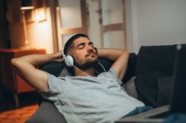 man relaxing in his apartment listening to a music