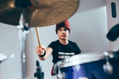 boy playing drums in music studio