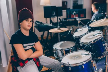 boy drummer crossed arms in music studio