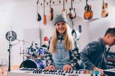 girl playing piano in music studio