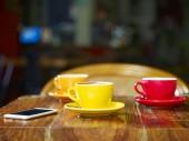 három csésze kapucsínó és a mobilját, a táblázat egy kávézóban