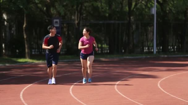 young asian couple jogging in stadium