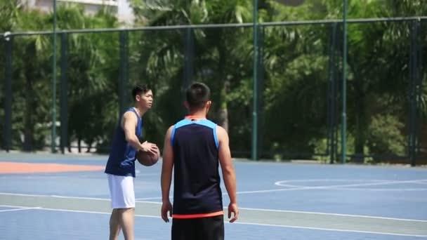 Asijské mladé dospělé hrát basketbal na venkovní kurt.