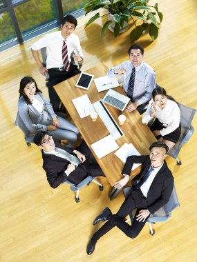 high angle view of a team of asian corporate executives looking at camera smiling.