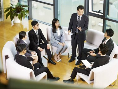 boss speaking to team of asian business people sitting in a circle during meeting in office.