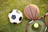 fotbal fotbalový míč basketbal tenisák a raketa kladen na trávě na západ slunce, closeup