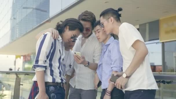 group of young asian adult men looking at cellphone together outdoors
