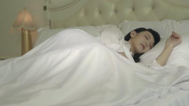 fiatal ázsiai nő alszik, és felébred az ágyban