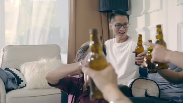 group of young asian adult men gathering drinking beer toasting at home.