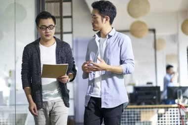 young asian coworkers discussing business in office