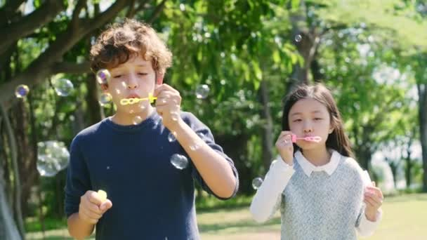 two children one italian one chinese having fun blowing bubbles outdoors in a park