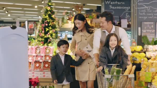 happy asian family with two children grocery shopping in supermarket