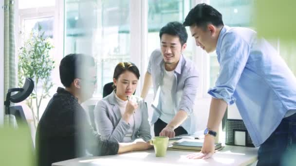 group of young asian business people men and woman meeting discussing in office