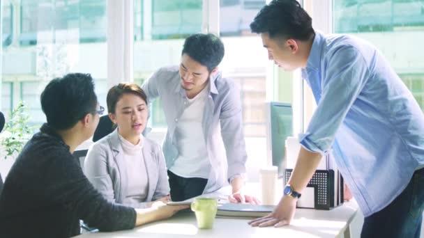 Gruppe von vier jungen asiatischen Geschäftsleuten trifft sich im Büro