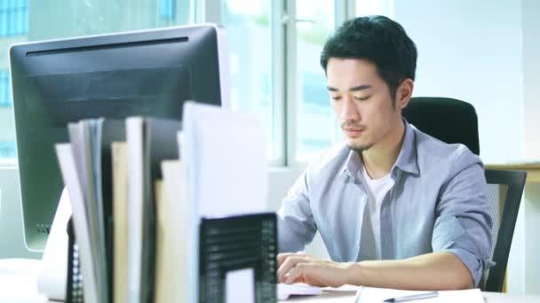 Junge asiatische Geschäftsfrau, die im Büro mit Desktop-Computer arbeitet