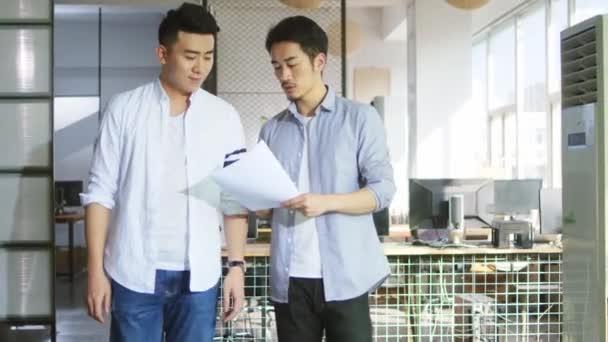 zwei junge asiatische Geschäftsleute analysieren Verkaufsbericht im Büro eines kleinen Unternehmens