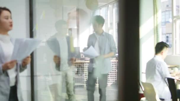 dva mladí asijští obchodní lidé diskutují o prodejním hlášení, jak se prochází v kanceláři