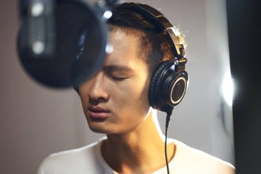 young asian musician recording songs in studio