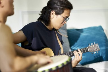 young asian guitarist playing guitar