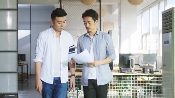 two young asian entrepreneurs discussing business while walking in office