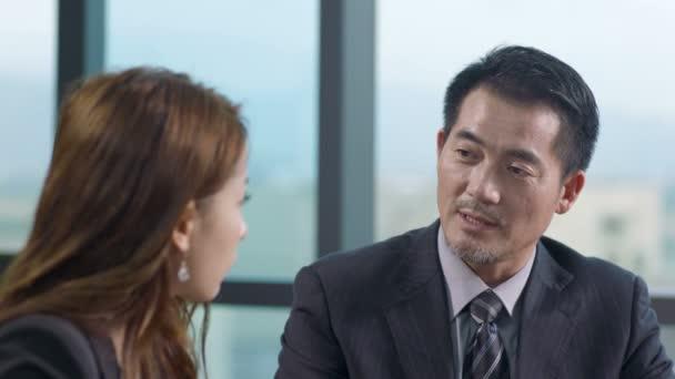 Asijské obchodní muž a žena mluví v kanceláři.