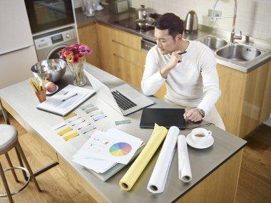 Genç Asyalı tasarımcı evden çalışıyor.
