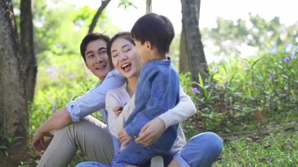 mladí asijské rodiče a dítě těší příroda venku v lese