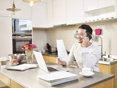 young asian business man sitting kitchen counter working at home looking at report talking on cellphone