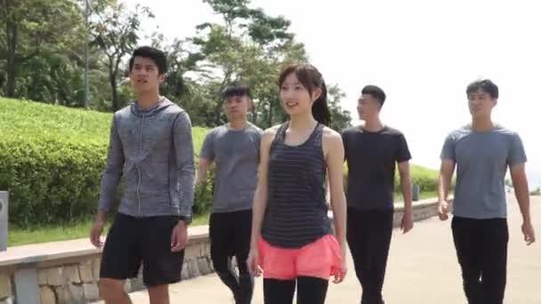 skupina pěti asijských mladých dospělých chůze mluvení relaxační venku po cvičení