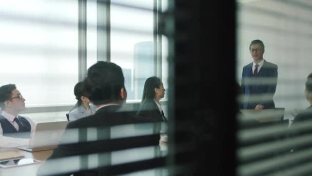 ázsiai főnök beszédet mond a csapat találkozó során a modern irodában