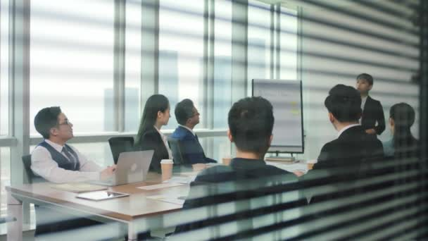 junior asian executive presenting business plan to team during staff meeting in modern office conference room