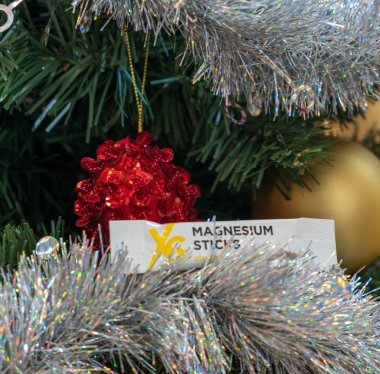 CAGLIARI, ITALY - DECEMBER 2018:XS Sport Nutrition magnesium stick on a christmas tree. Nutrilite natural and vegan supplements. Natural supplements for athletes for a healthy and flexible lifestyle.
