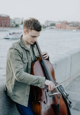 Street musician, young man playing cello in the street of big city, Moscow, Russia