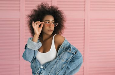 Cheerful  African American woman with beautiful sexy body posing for pictures and standing near pink background. Young curly hair hipster girl wearing stylish jacket and eyeglasses in showroom. Shopping. Eyebrow makeup.