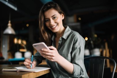 Cheerful woman using mobile phone for online banking, shopping web, learning language sitting in loft coffee shop. Positive caucasian student holding modern smartphone and making notes to study. Online education.