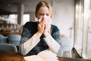 Young blonde woman feeling bad, using  handkerchief. Allergy. Sickness. Infection. Virus. Flu