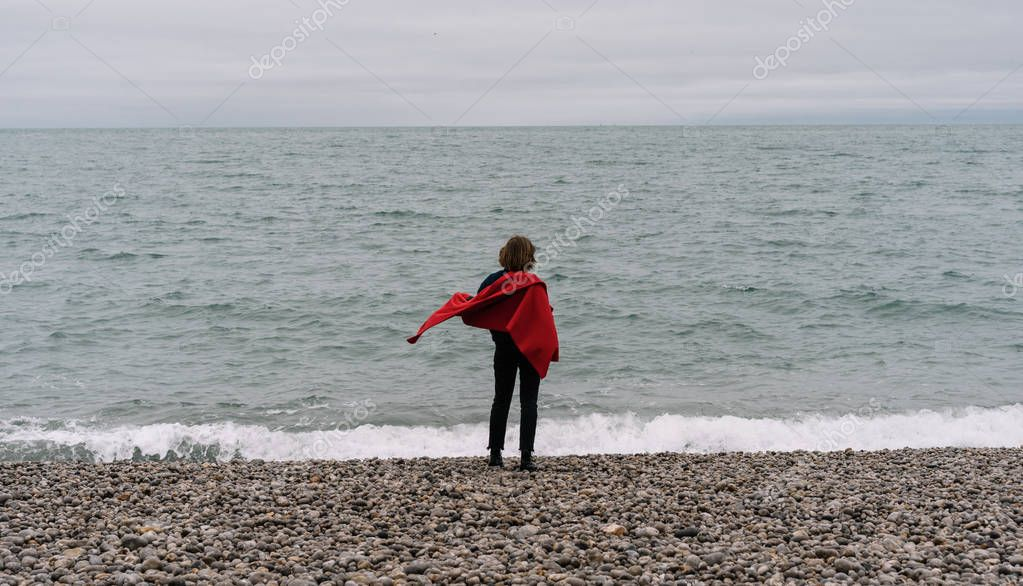 Back view of woman traveler with red cape standing on the ocean beach, dreaming and enjoying beautiful landscapes. Travel concept. Vacation.