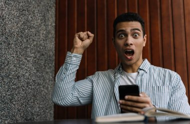 Overjoyed African American man with happy emotional face, open mouth and eyes win online poker jackpot. Guy using mobile app for online shopping with discount sales, cash back, low prices. Black Friday concept