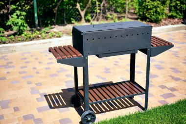 barbecue grill on wheels with wooden stands in the garden. tasty and wholesome food in the heat. future shish kebab. for holidays and events. bright sun.