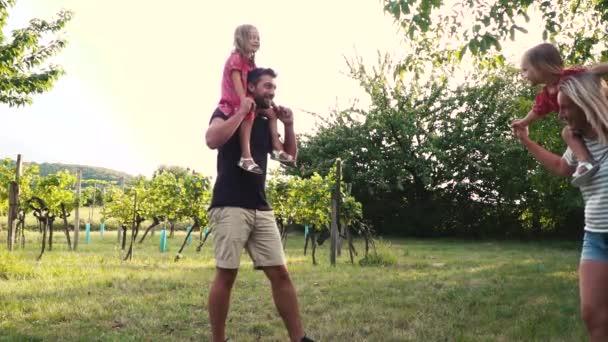 Mladá rodina s dvěma holkama baví v sadech při západu slunce