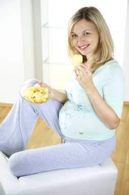 happy pregnant woman sitting on armchair and eating chips at home