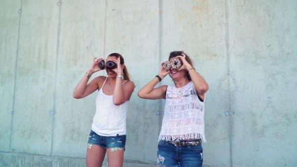 dvě krásné ženy se baví s koblihy stoje betonové zdi
