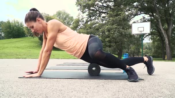 young woman training on foam roll at stadium