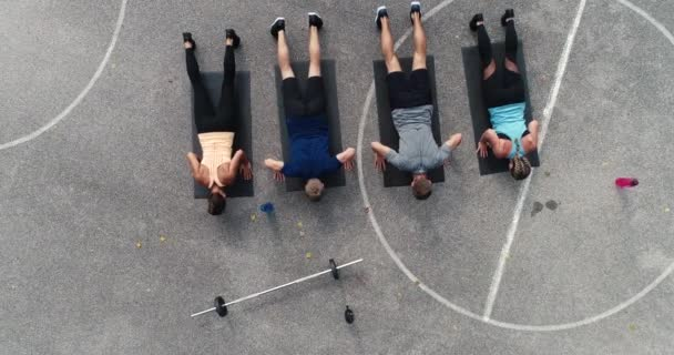 two women with two men doing push ups at stadium, top view