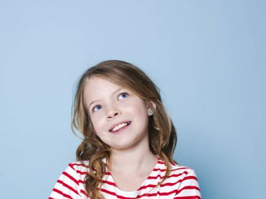 portrait of pretty girl with curly hair in striped t-shirt smiling and looking up in front of blue background