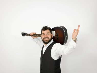 man with black hair and beard posing with acoustic guitar on white background