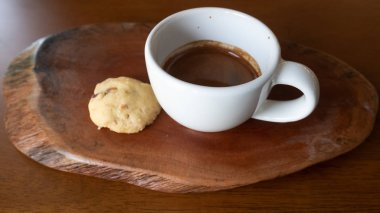 Hot coffee. A cup of hot coffee. Espresso coffee and biscuit on wooden table