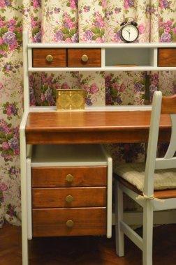 Wooden table with drawers and chair in a room on the background of curtains with flowers