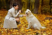 Beautiful brunette woman drinking coffee with golden retriever in autumn park.