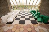 Fotografie v budově je velké šachovnici na podlaze s umělými objekty